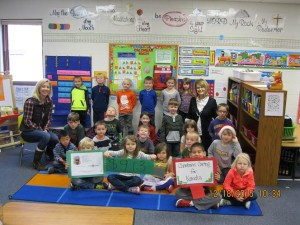 Excited kindergarteners happily show the sign of $913 for Komeka!
